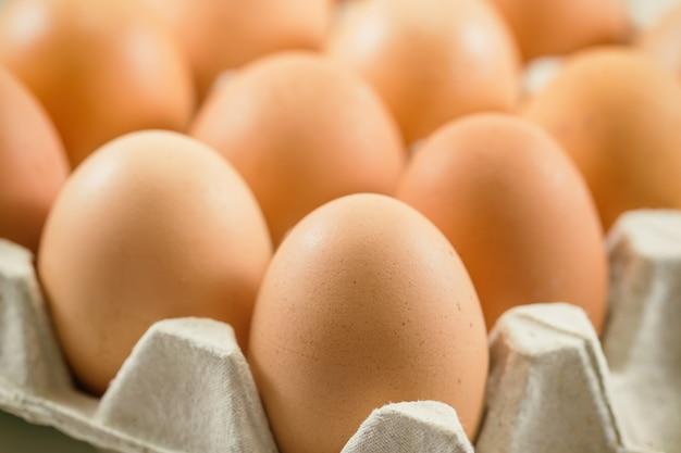 Ovos frescos em cremalheira do ovo colocar na mesa de madeira, preparar para cozinhar ou padaria