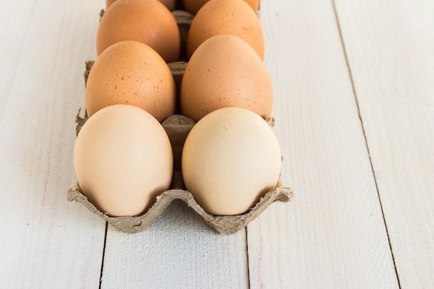 Ovos frescos em embalagem de cartão em madeira branca