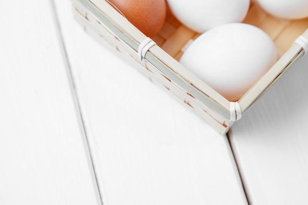 Ovos frescos em uma cesta em um fundo de madeira.