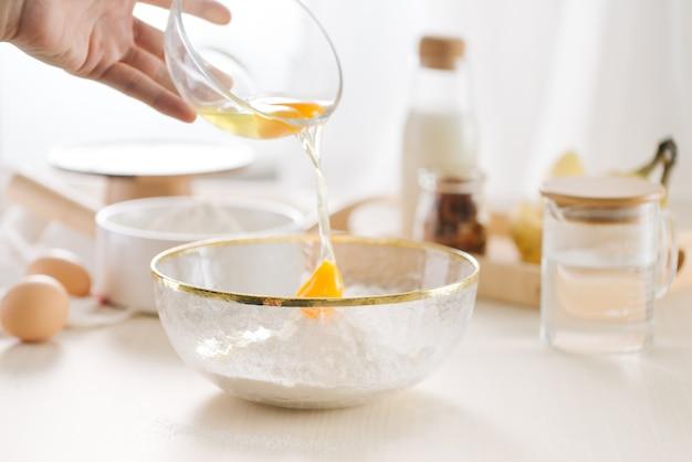 Ovos frescos, leite e farinha na mesa branca