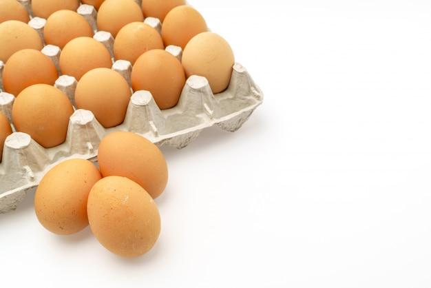 Ovos frescos no pacote no fundo branco.