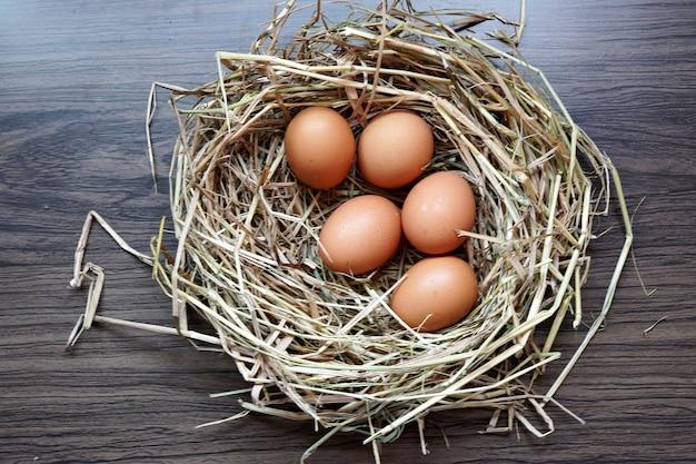 Ovos frescos orgânicos em um ninho marrom em uma mesa de madeira