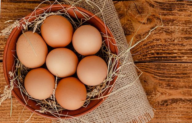 Ovos frescos orgânicos em uma tigela no espaço rústico de madeira. diretamente acima, copie o espaço.