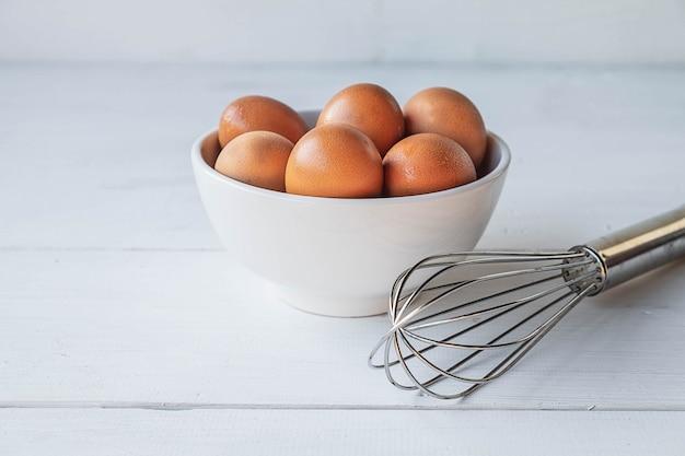 Ovos frescos para cozinhar em uma mesa de madeira branca