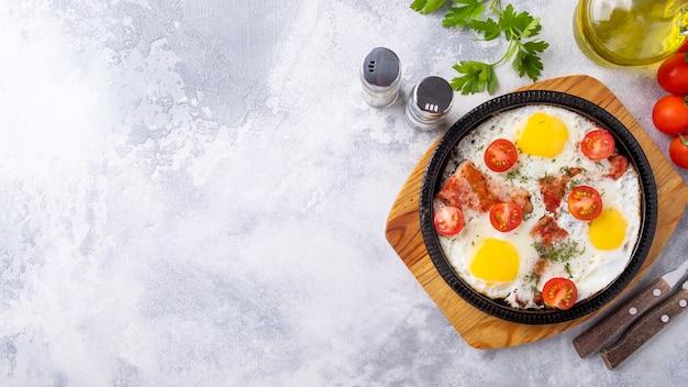Ovos fritos, bacon e vegetais em uma frigideira