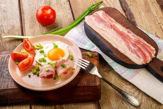 Ovos fritos com bacon com tomate e cebola verde e em uma mesa de madeira em um prato ao lado de bacon e tomates picados foto horizontal