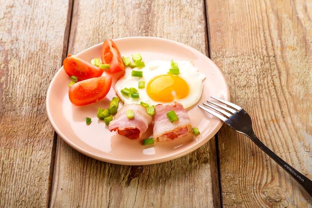 Ovos fritos com bacon com tomate e cebola verde e em uma mesa de madeira em um prato