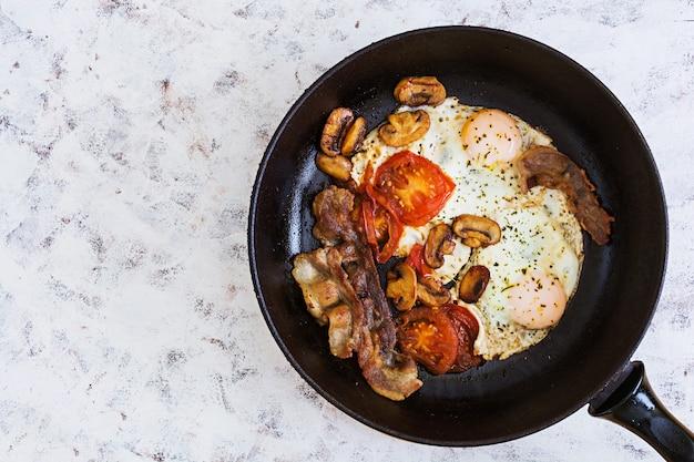 Ovos fritos com bacon, tomate e cogumelos