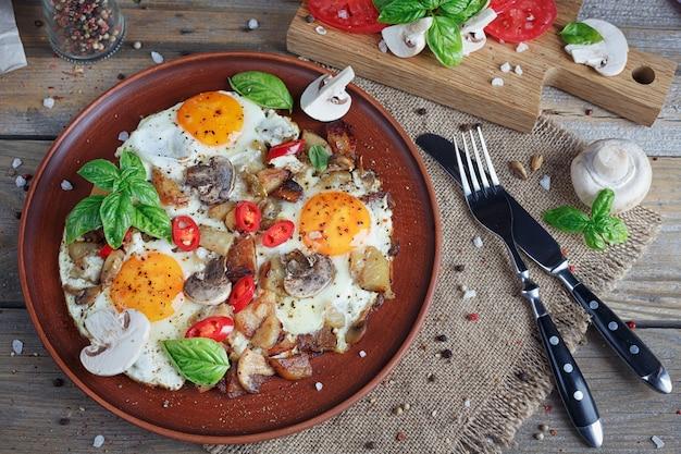 Ovos fritos com cogumelos, tomate e manjericão na mesa de madeira rústica.