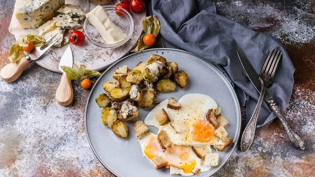 Ovos fritos com croutons, brotos, manteiga, queijo e uma baguete com sementes de abóbora