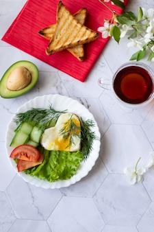 Ovos fritos com fatias de alface, pepino e tomate em um fundo claro