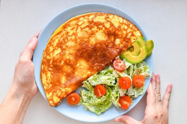 Ovos fritos com legumes. mãos no quadro. omelete de legumes em um prato azul sobre uma mesa branca, vista superior
