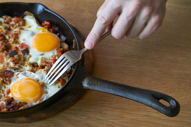 Ovos fritos com legumes na frigideira e mão masculina com garfo na mesa de madeira