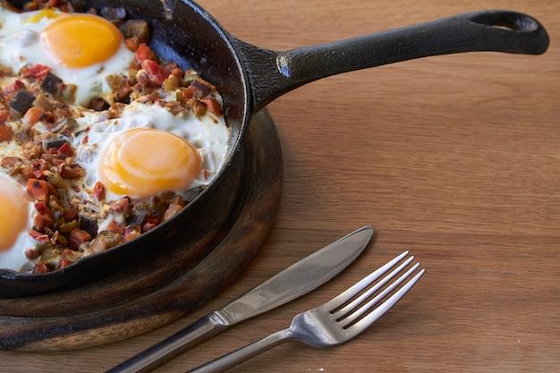 Ovos fritos com legumes na frigideira, faca e garfo na mesa de madeira