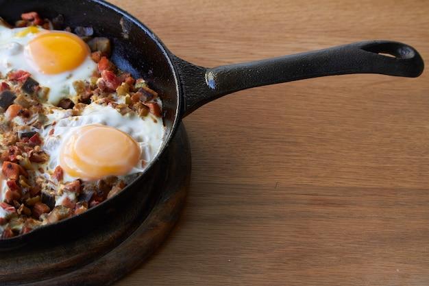 Ovos fritos com legumes na frigideira na mesa de madeira