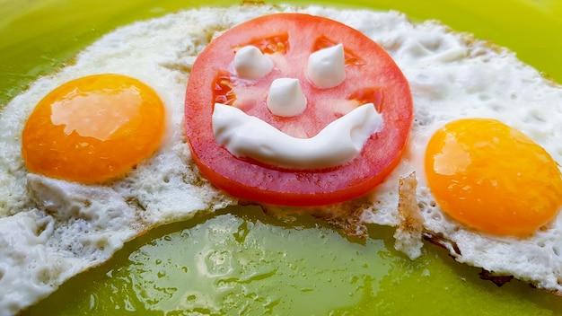 Ovos fritos com legumes num prato verde, servidos às crianças.