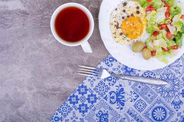 Ovos fritos com salada verde e uma xícara de chá.