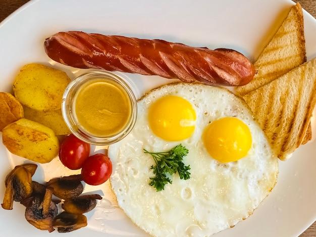 Ovos fritos com salsicha e torradas num prato. estilo leigo plano. saboroso café da manhã