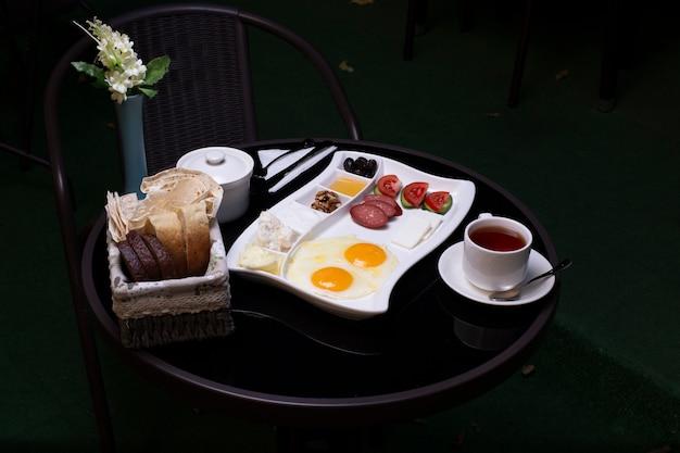 Ovos fritos com salsichas, azeitonas, queijo, pão e uma xícara de chá na mesa preta
