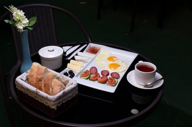 Ovos fritos com salsichas, azeitonas, queijo, pão e uma xícara de chá