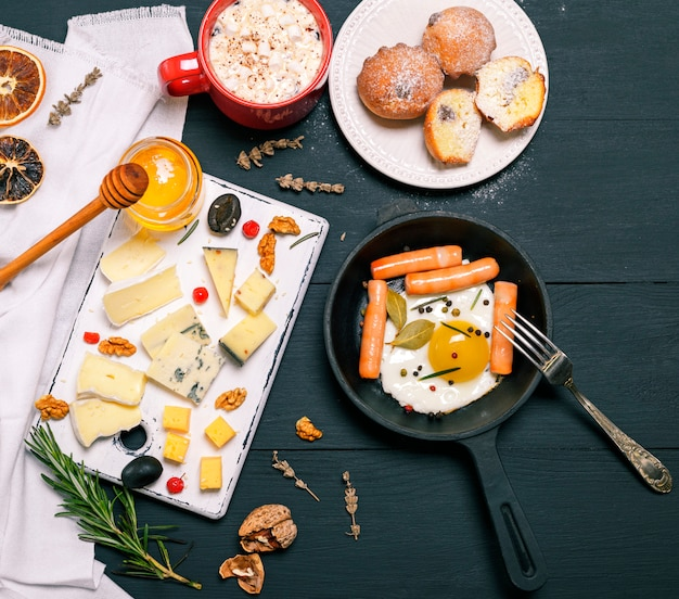 Ovos fritos com salsichas em uma frigideira redonda preta e tábua de queijos