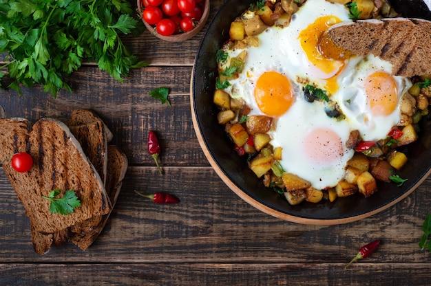 Ovos fritos com shakshuka de legumes em uma frigideira e pão de centeio em um fundo de madeira