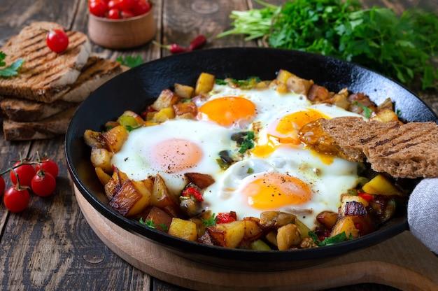 Ovos fritos com shakshuka de vegetais em uma frigideira e pão de centeio