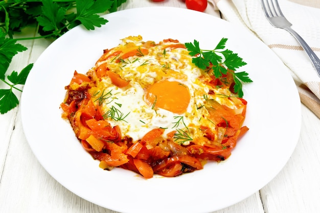 Ovos fritos com tomate, pimentão, cebola e ervas em um prato, guardanapo, salsa e garfo no fundo
