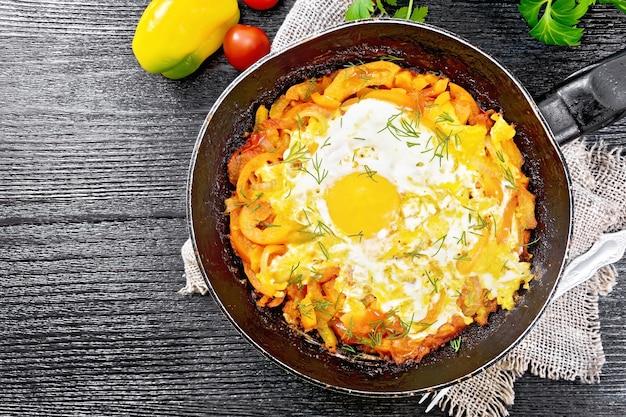 Ovos fritos com tomate, pimentão, cebola e ervas em uma panela na serapilheira, salsa, garfo na placa de madeira