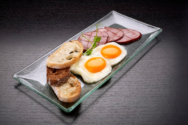 Ovos fritos com torradas de tomate, presunto e ciabatta, em superfície escura. café da manhã