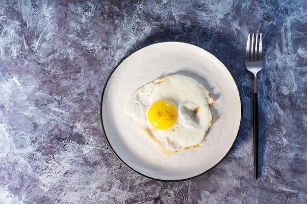 Ovos fritos em close-up de placa branca. vista de cima.