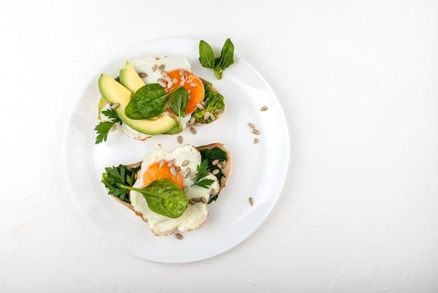 Ovos fritos em um brinde pão com abacate, espinafre e sementes em um prato branco.