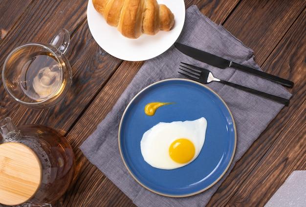 Ovos fritos em um prato azul em uma mesa de madeira café da manhã com um croissant vista de cima