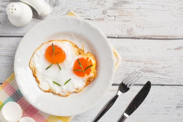 Ovos fritos em um prato branco em uma superfície de madeira branca