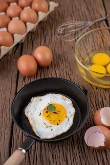 Ovos fritos em uma frigideira e ovos crus, alimentos orgânicos para uma boa saúde, ricos em proteínas