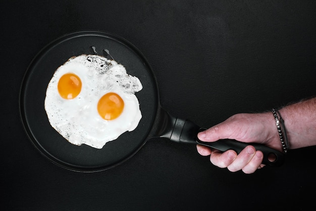Ovos fritos em uma frigideira na mão masculina em fundo preto, copie o espaço