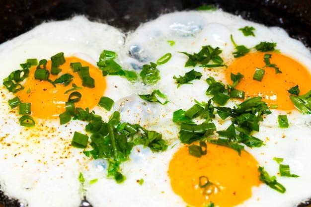 Ovos fritos em uma frigideira no café da manhã em um fundo preto