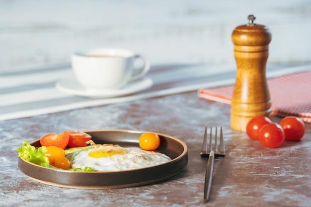 Ovos fritos em uma panela com tomate cereja e café no café da manhã