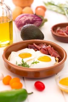 Ovos fritos em uma xícara de cerâmica com jamon espanhol no café da manhã