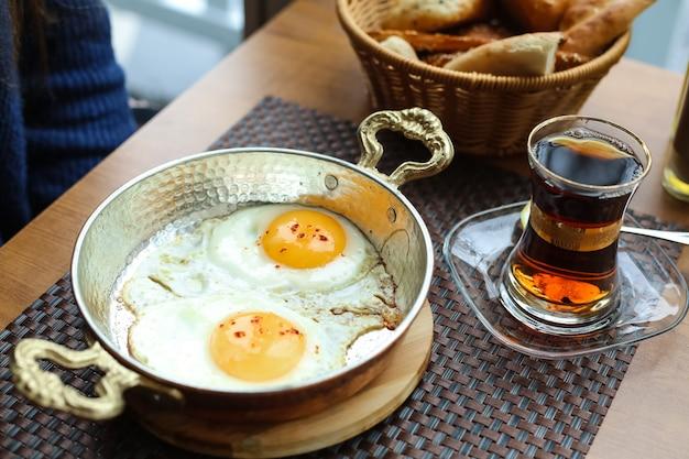 Ovos fritos na frigideira na tábua de madeira chá no pão armudy