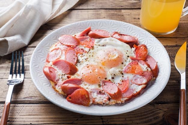 Ovos fritos salsichas e tomates em um prato na mesa. fundo de madeira fechar-se