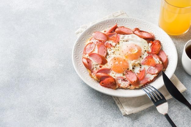 Ovos fritos salsichas e tomates em um prato na mesa.
