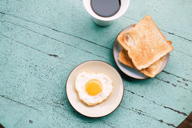 Ovos fritos, torradas, café, café da manhã colocado em uma mesa de madeira azul