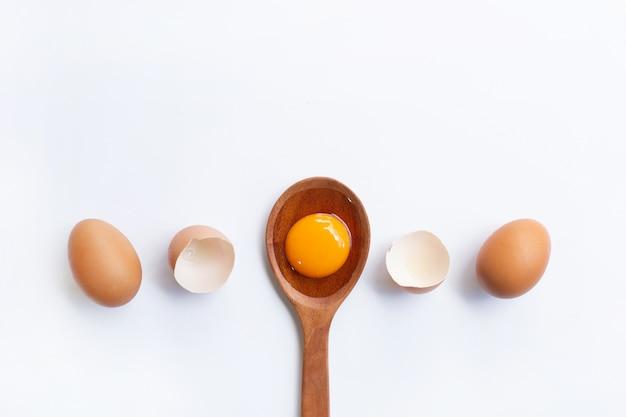 Ovos, gema na colher de madeira isolada no fundo branco.