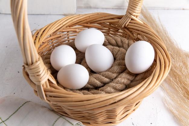 Ovos inteiros brancos de vista frontal dentro da cesta no fundo branco.