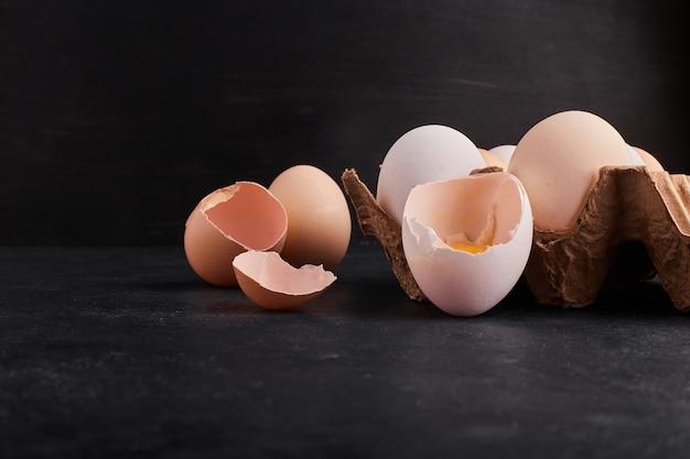 Ovos inteiros e cascas de ovo em bandeja de papelão.
