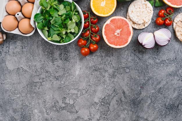 Ovos; legumes; frutas cítricas e bolo de arroz no fundo de concreto