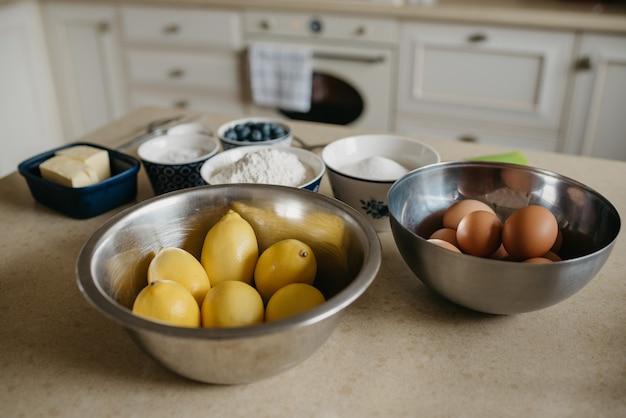 Ovos, limões, dois pedaços de manteiga, mirtilos, farinha de trigo, farinha de amêndoa e açúcar estão se preparando para a torta de merengue de limão na cozinha