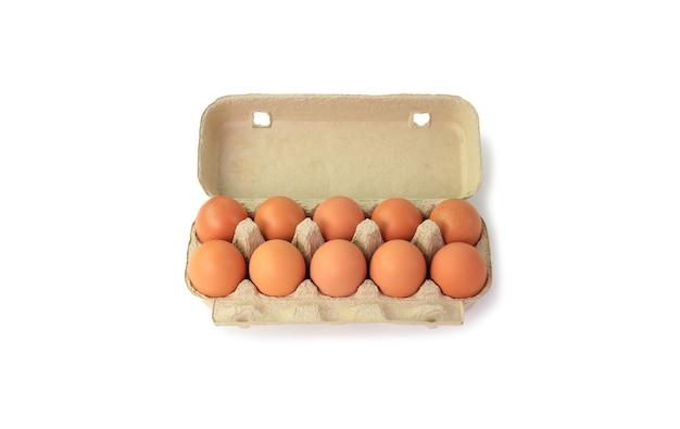 Ovos marrons de frango em caixa de papelão, isolados no fundo branco com traçado de recorte