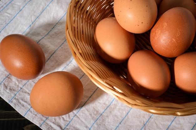 Ovos marrons frescos em um fundo escuro, de madeira, preto, escuro em uma cesta